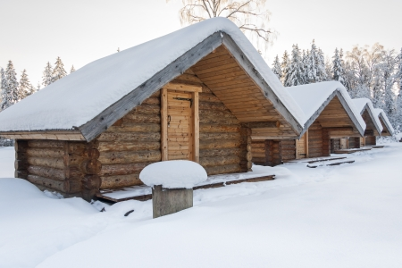 Small snowy cosy log cabins in row at very snowy winter day photo