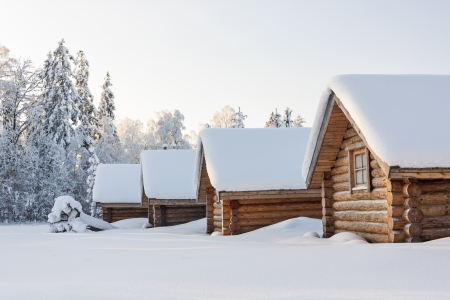 Small snowy cosy log cabins in row at very snowy winter day