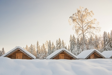 maisonette: Small snowy cosy log cabins in row at very snowy winter day