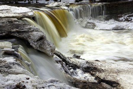 joa: Flowing waterfall called Keila Juga in Estonia with large piece of ice and melting snow at winter  Stock Photo
