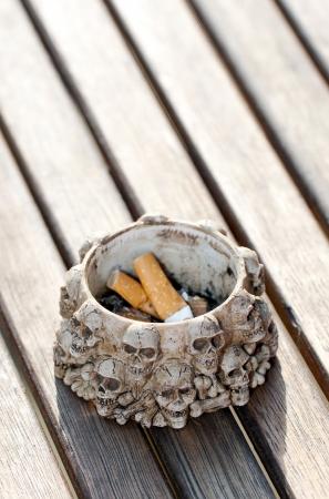 injurious: Colillas de cigarrillos y cenicero decorado con figuras de cr�neos humanos