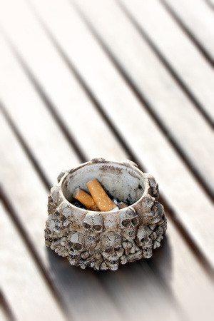 unwholesome: Cigarette ends and ashtray decorated with human skull figures