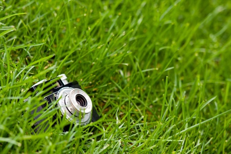 Old classical Russian made film camera known as Cmena on the ground at green grass Stock Photo - 16798678