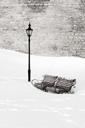 Two wooden and metal park benches in deep white snow near street lantern at winter  Limestone wall in the background  Stock Photo