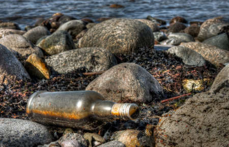 Glass made old alcohol bottle left onto rocks near water Stock Photo - 17788394