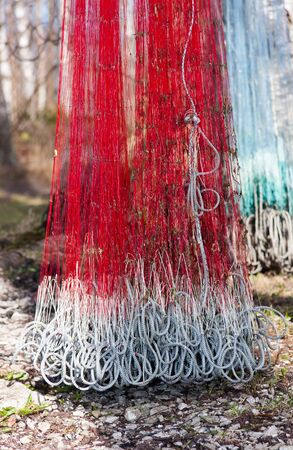 Hanging dirty red fishing net  Greenish net at the left side on background  Stock Photo - 17789206