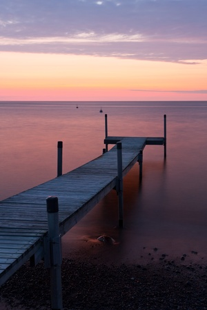 Long wooden bridge leading from ground into the sea at sunset at calm weather Stock Photo - 17963128