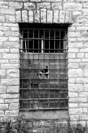 Old grated prison window in limestone wall photo