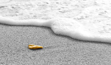 foamy: Yellow rock on sand in front of foamy water wave