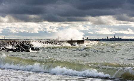 turbulent: Pier or quay in a stormy and turbulent sea at a gloomy but but sunny day. City silhouette of Tallinn in background. Stock Photo