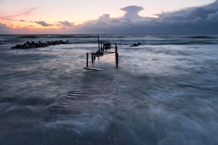 foot bridge: Timber foot bridge in sea and partly under water due to high tide at sunset