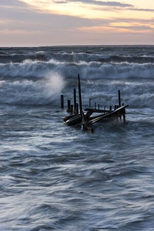 foot bridge: Broken timber foot bridge in sea and partly under water due to high tide at sunset