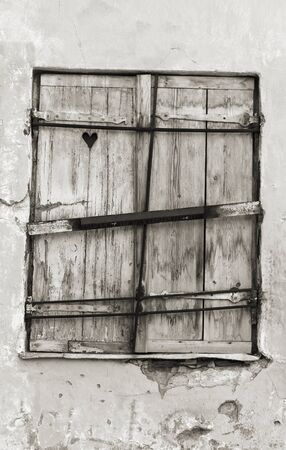 Old wood made window hatch or shutter with heart shape in it Stock Photo