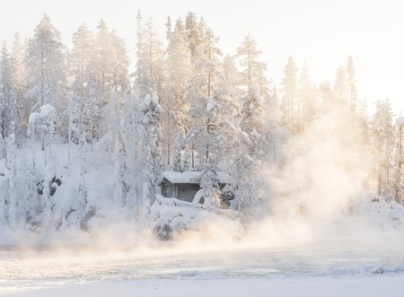 Small log cabin behind vaporing river in winter in Lapland, Finland photo