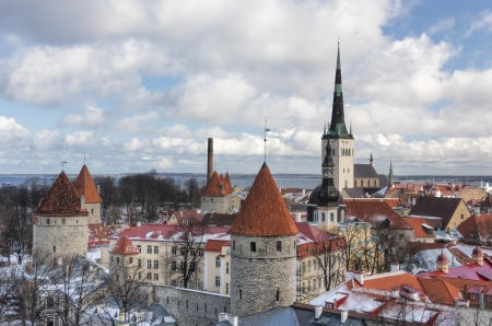 historic Old Town of Tallinn, capital of Estonia. Roofs are covered with snow. Church St. Olaf (Oleviste) at background, curtain wall with towers in foreground. photo