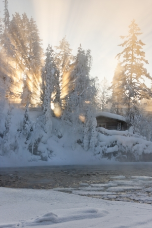 Hut near water and misty forest in winter in Lapland, Finland