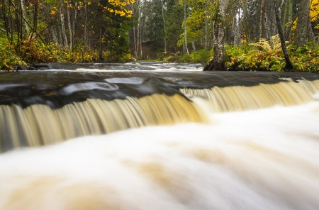 Little waterfall or cascade in autumn forest