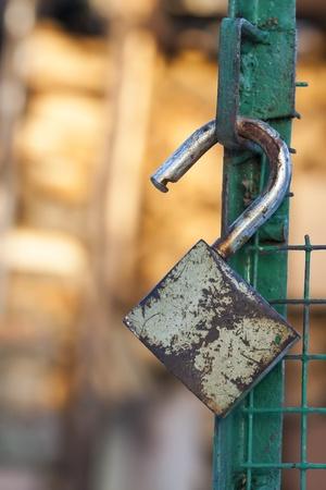 Open badlock hang on a green gate Stock Photo