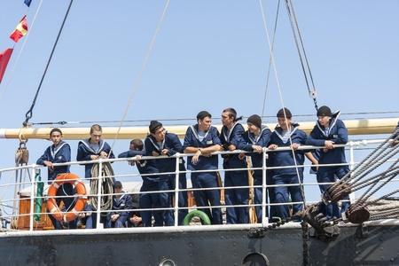 TALLINN, ESTONIA - JULY 12, 2013: Crew of the Kruzenshtern or Krusenstern sail ship lean on handrail after arriving to Tallinn Maritime Days on July 12, 2013 in Tallinn, Estonia
