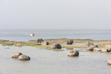 oar: White oar boat in misty sea near rocky coast