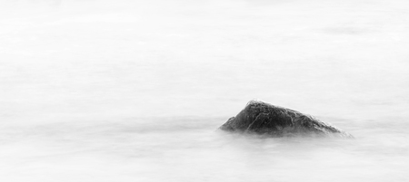 waterscape: Single stone or rock in a blurry sea Stock Photo