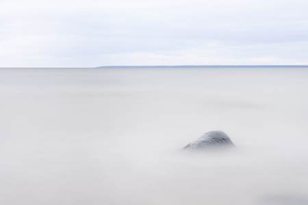 Single stone or rock in a blurry sea, isle on background at horizon Stock Photo