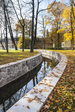 Water canal or conduit in a park in autumn, houses in background