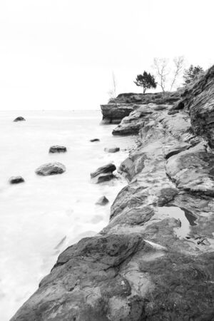 Cliff near sea and several rocks in water on a overcast day