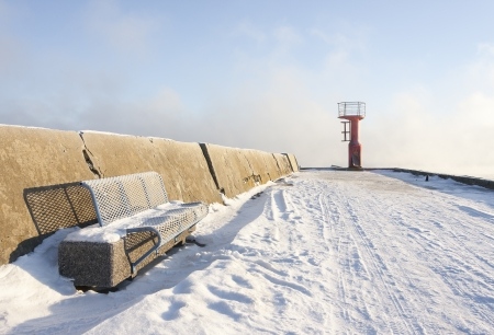 Blue metal bench on snowy mole and small beacon or lighthouse at the end of the pier