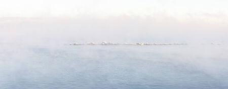 Stone made pier in heavily vaporing sea in winter