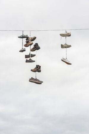 Many old worn boots or shoes hang on an electric cable Stock Photo