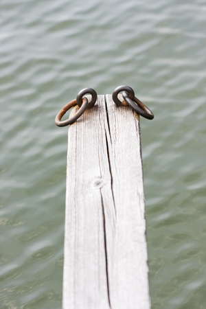 loops: Iron loops on top of a timber beam to tie boats to it Stock Photo