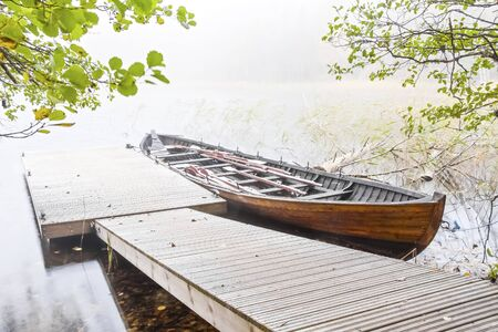 oar: Long wood oar boat parked next to floating quay in a mist
