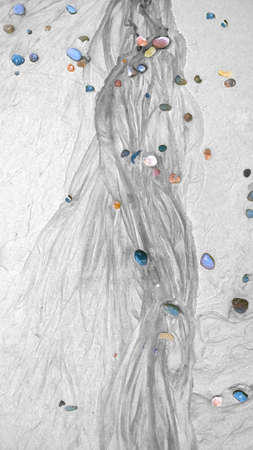 water flow: Colorful stones on sand covered with water flow tracks