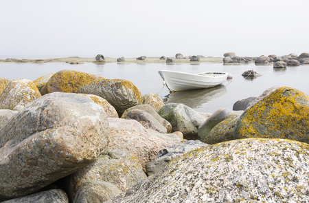 large rocks: White boat in a shore behind large rocks, fog in the background