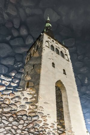 Reflection of St. Olaf church tower on water in Tallinn, Estonia