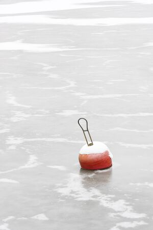 Red snowy marine buoys in frozen sea water at winter Stock Photo
