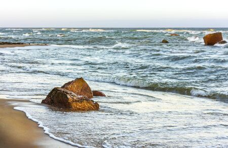 Stormy seascape of several rocks in a turbulent ocean, sandy beach at foreground Stock Photo