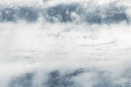 Island far in distance in a vaporing sea Stock Photo