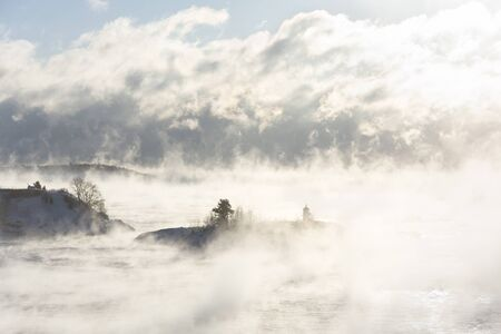 Small island with a lighthouse in misty vaporing ocean at winter