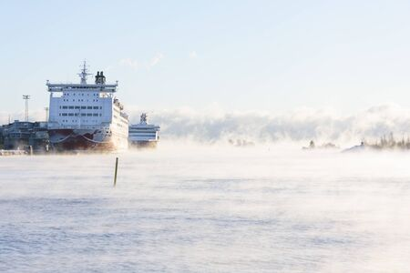 Two cruise ships in a cold steaming sea