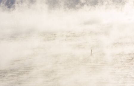 Small marine buoy or sea mark in a very misty vaporing sea at winter Stock Photo