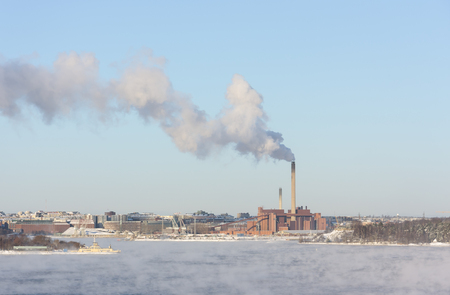 Factory with a tall smoking chimney behind vaporing water at winter