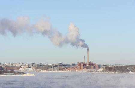 tall chimney: Factory with a tall smoking chimney behind vaporing water at winter