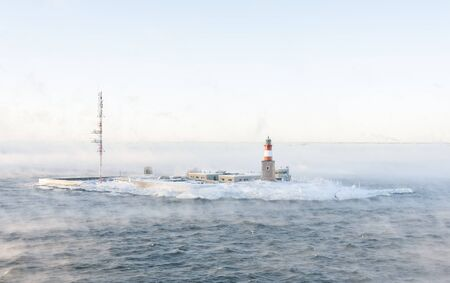 Lighthouse and telecommunication antenna on an isle in a vaporing sea at winter Stock Photo