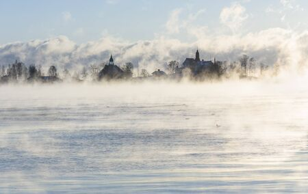 Island with buildings in a steaming ocean Stock Photo