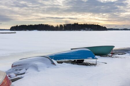 Several colorful oar boats in harbor at winter