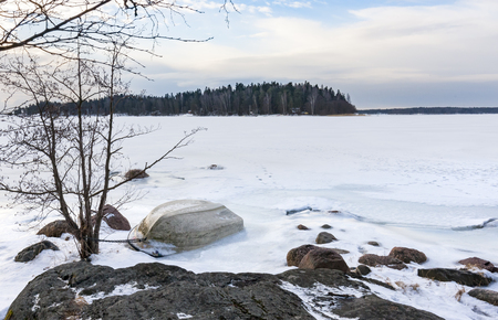 Small white oar boat upside down on frozen sea