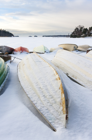 Snowy boats in harbor upside down at winter