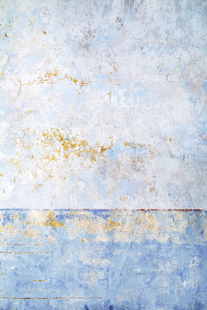 Architectural background of an old blue wall with scratched or fallen off paint